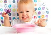 foto of child feeding  - cheerful happy baby child eats itself with a spoon - JPG