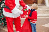 Midsection of Santa Claus giving gift to boy outside house