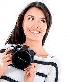 Thoughtful female photographer holding a camera - isolated over white