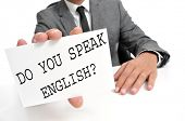 a man wearing a suit holding a signboard with the sentence do you speak english? written on it