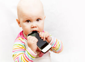 stock photo of nic  - little baby baby chews on a mobile phone in colorful clothing - JPG