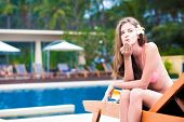 beautiful young woman in bikini on chaise-longue blowing air kiss