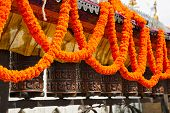 Prayer Wheel And Garlands Of Flowers