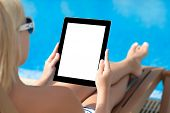 Girl In A Bathing Suit Lying On A Sun Lounger By The Pool With A Computer Tablet