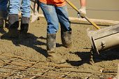 stock photo of concrete pouring  - Workers pouring a concrete pad outside a new commercial building - JPG