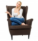 Young girl talks by mobile phone in chair isolated