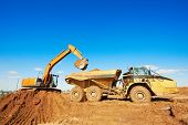 stock photo of backhoe  - wheel loader excavator machine loading dumper truck at sand quarry - JPG