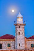Ciutadella Menorca Punta Nati lighthouse with moon shining in sky