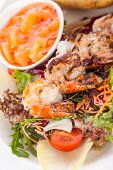 pic of endive  - Grilled prawns with a green leafy lettuce and endive salad and a jacket potato topped with sour cream served on a white plate close up high angle view on white - JPG