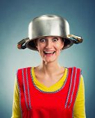 Happy housewife with sause pan on her head