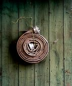 stock photo of firehose  - Fire hose hanging on a wooden wall - JPG