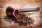 stock photo of tobacco-pipe  - Grunge wooden texture with smoking pipe and tobacco on linen canvas - JPG