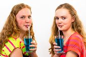 Two teenagers drink blue soda