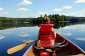 Young girl in canoe paddling on a scenic lake
