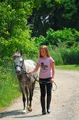 Young girl walking with a pony on a farm road