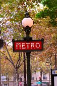 Red metro sign in Paris France on background of fall trees