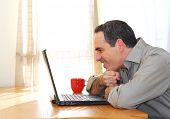 Man sitting at his desk with a laptop looking happy
