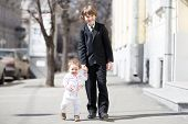 Brother And Sister Wearing Formal Clothes Walking On A Sunny Street