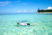 Young Man Snorkeling Next To A Beautiful Tropical Island