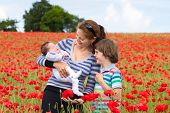 Young Mother With Her Son And Newborn Baby In A Beautiful Red Flower Field