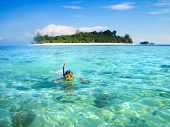Little Boy Snorkeling Next To A Beautiful Tropical Island