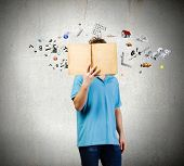 Young man in casual holding opened book with icons flying out