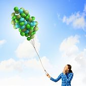 Young woman in casual holding bunch of colorful balloons