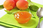 bowl of apricot jam and ripe apricots on green napkin