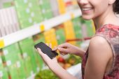 stock photo of supermarket  - Smiling young woman at supermarket using mobile phone and looking at camera - JPG
