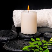 Spa Setting Of Green Branch Fern, Towels And Candle On Zen Stones With Drops , Closeup