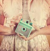 Woman holding vintage mint green camera. Instagram effect.