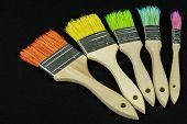 Colorful brushes arranged in an arc on an isolated black background