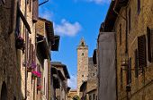 Medieval architecture of San Gimignano, towers and houses decorated with flowers, Tuscany
