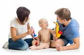 Mother, Father And Baby Boy Play Musical Toys. Isolated On White Background