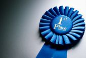 pic of rosettes  - Blue first place winner rosette or badge from pleated ribbon with central text to be awarded to the winner of a competition on a graduated grey background with copyspace - JPG