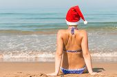 Girl In A Santa Claus Hat On The Beach