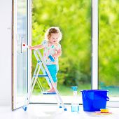 picture of window washing  - Cute laughing curly toddler girl washing a big window with a squeegee in beautiful white living room with door into the garden standing on a ladder next to a blue bucket with water detergent solution spray bottle and sponge - JPG