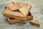 Tangram, a traditional Chinese Puzzle Game made of different wood parts to build abstract figures fr