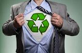 Businessman in classic superman pose tearing his shirt open to reveal t shirt with recycling symbol