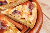 baked food : apple pies on wooden plate over table with cinnamon sticks and lemons