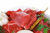 slices of raw fresh beef meat fillet in a white bowls with garlic and red peppers isolated over whit