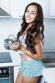 beautiful young woman cooking in the kitchen at home