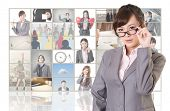 Attractive Asian business woman standing in front of TV screen wall, closeup portrait.
