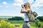 Hiker looking in binoculars enjoying spectacular view on the valley. Young woman using binoculars in