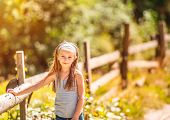 beautiful little girl near a wooden fence in the countryside