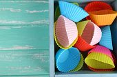Plastic bowls in wooden box on color wooden background