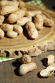 Peanuts in bowl on rustic wooden background
