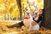 young woman relaxing in autumn park with dogs