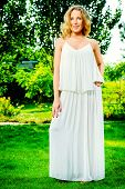 Full length portrait of a beautiful woman in light white dress standing in the summer park. Beauty,