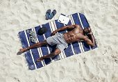 pic of sunbather  - Top view of muscular young man sunbathing on beach - JPG